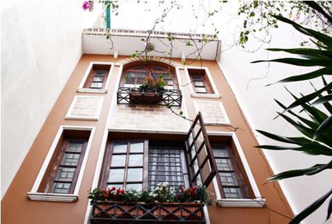 Ngôi nhà với một trệt, 2 lầu, mang dáng dấp kiến trúc Đức, màu nâu chủ đạo trên nền kem nhạt.