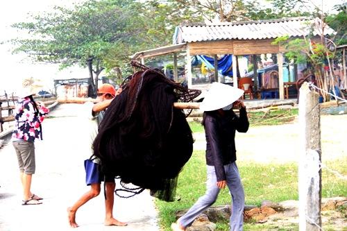 ngư dân trong xóm Cồn Đâu tranh thủ thu dọn ngư cụ tránh bão. Ảnh: Phúc Nguyễn