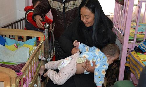 Dù bệnh tật, bà Li vẫn tự tay chăm sóc những đứa trẻ mình cưu mang. Ảnh: Shanghaiist.