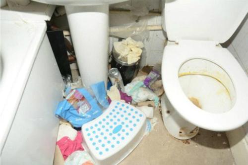 Bồn cầu cáu vàng và sàn nhà vệ sinh đầy rác.