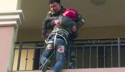 Lính cứu hỏa đưa cậu bé từ ban công tầng dưới lên nhà mình ở tầng 3. Ảnh: Scmp.
