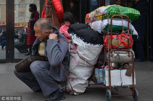 Ông Wang vác 200 kg đồ đạc, hoa quả quê lên thành phố đoàn tụ vợ con. Ảnh: Chinanews.