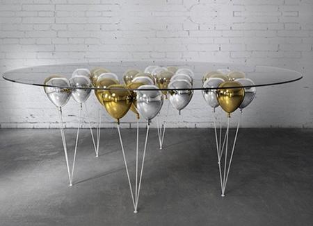 Chiếc bàn kính trở nên bay bổng hơn khi chân bàn là những chùm bóng được sơn tông màu xám bạc và đồng sang trọng.
