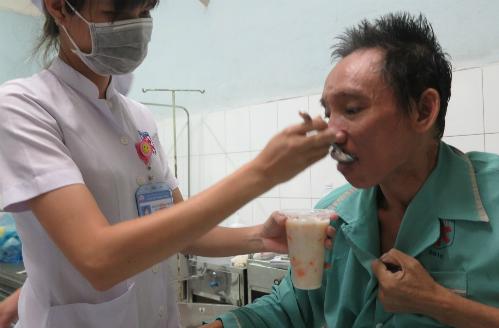 Sau hơn hai tuần được bệnh viện chăm sóc, ông Cảnh đã có thể ngồi dậy, tự xúc ăn. Ảnh: Phan Thân
