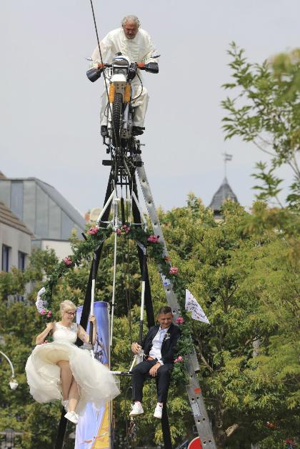 Dâu rể được nghệ sĩ đi trên dây phía trên kéo đến trước linh mục làm lễ. Ảnh: Dw.