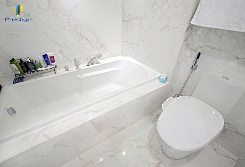 Phòng tắm có bồn tắm nằm, khu vực giặt, sấy tinh gọn. Nền và tường ốp đá cẩm thạch trắng với các vân đá tự nhiên giúp mang lại không gian sáng rộng.Toàn bộ ngôi nhà thiết kế và thi công bởi công ty thiết kế nội thất Prestige.