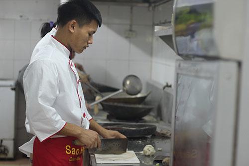 Các học viên đang thực hành các bài học nhập môn về cách thái, đảo khi tham gia lớp đầu bếp tại trung tâm của anh Trương Công Lệ. Ảnh: MT.