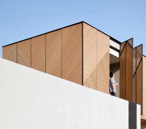 Nhà được bao bọc bởi những mảng gỗ chéo, vừa tạo sự riêng tư, vừa lấy ánh sáng tự nhiên cho cả căn.