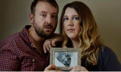 Vợ chồng anh Hughes với bức ảnh con trai Riley. Sau cái chết của con trai mình, vợ chồng anh đã vận động các cha mẹ hãy cho con tiêm phòng ho gà. Ảnh: News Limited.
