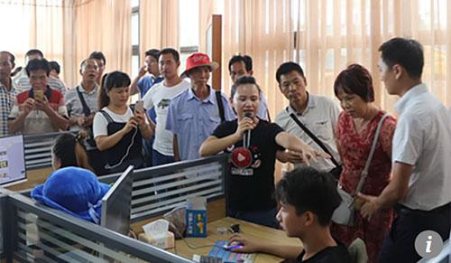 ChịGan Youqin (mặc áo đen, cầm mic)đang giới thiệu về mô hình làm việc của nhóm mình với các quan chức tỉnh. Ảnh: Scmp.