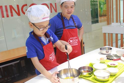 Ông bố duy nhất trong lớp học, anh Long (quận Hoàng Mai) cùng con trai Trung Nguyên (8 tuổi). Cậu bé hào hứng thực hành làm bánh cùng bố.