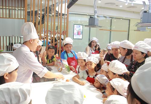 Thầy giáo hướng dẫn các bạn nhỏ làm hỗn hợp tạo màu cho bánh.