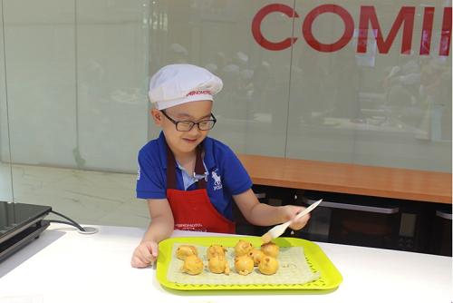 Trung Nguyên 8 tuổi, tự tay quết lớp hỗn hợp tạo màu chuẩn bị nướng bánh lần thứ ba. Lần nướng này giúp làm chín và để bánh có màu đẹp.