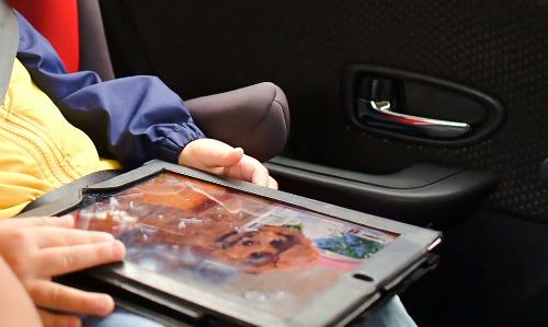 Nhiều trẻ em được cha mẹ cho cầm chơi máy tính bảng khi ngồi trên ô tô. Ảnh: Videoblocks.