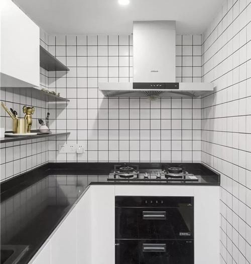 Khu bếp nhỏ dạng chữ L ốp gạch subway trắng miết mạch đen nổi bật.