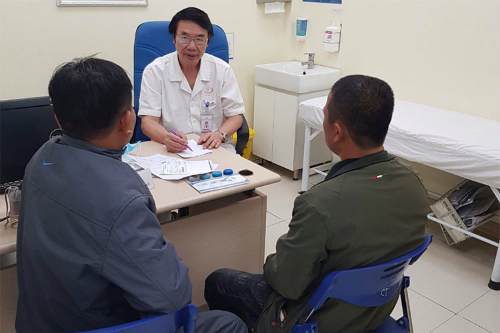 Bác sĩ Lợi tư vấncho một người cao tuổi được con trai đưa tới khámkhi gặp các trục trặc về sức khỏe nam giới.Ảnh: KL.