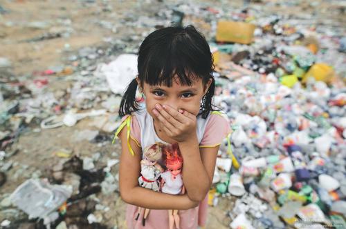 Bé Ngà, 9 tuổi và những con búp bê nhặt trên bãi rác - nơi sinh sống của gia đình em. Ảnh: Đinh Chí Trung.