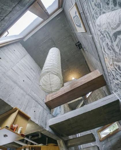 Không gian chật hẹp trong nhà được kiến trúc sư sắp xếp gọn gàng, tận dụng tối đa khoảng trống để treo các kệ gỗ, đèn...