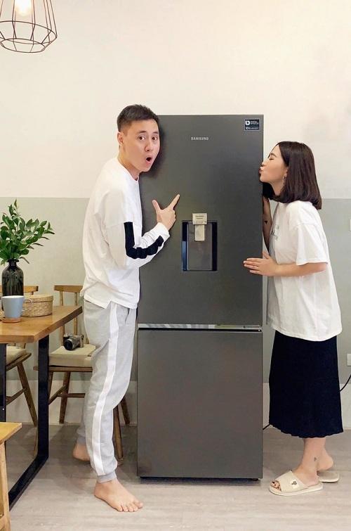 Vợ chồng Kiên Hoàng và Heo Mi Nhon tham khảo khá nhiều bí quyết nấu ăn nhanh và quyết định sắm chiếc tủ lạnh Samsung ngăn đông dưới mới. Tủ lạnh với thiết kế ngăn đông mềm Optimal Fresh Zone nhiệt độ chuẩn -1 độ C có khả năng giữ thịt cá tươi ngon đến 14 ngày, đảm bảo hương vị tươi ngon và dinh dưỡng cho gia đình. Mức nhiệt độ này đã được kiểm chứng từ Tổ chức kiểm định chất lượng sản phẩm Intertek (Anh).Nhờ vậy, bố của bé Cam có thể trữ thịt cá hay các loại thực phẩm tươi sống khác, không cần rã đông mà vẫn mềm mịn. Quan trọng hơn, nam diễn viên không lo thực phẩm có thể bị nhiễm khuẩn khi rã đông bằng cách ngâm nước.