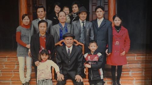 Ông Kính (giữa) và vợ (bên trái ghế) cùng con cháu. Ảnh: NVCC.