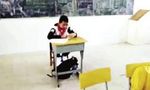 Hình ảnh cậu bé ngồi cách xa các bạn trong lớp khiến bố mẹ bé xót xa.