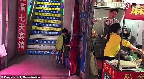 Cậu bé 10 tuổi học trong điều kiện thiếu sáng, trong khi cha mẹ bán hàng ăn. Ảnh: Peoples daily.