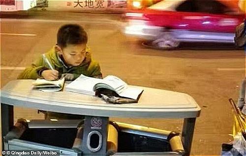 Cậu bé đi theo mẹ bán khoai lang và học ở lề đường.
