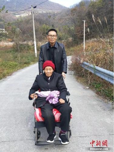 Một trong số những người con đẩy mẹ say xe. Ảnh: Chinanews.