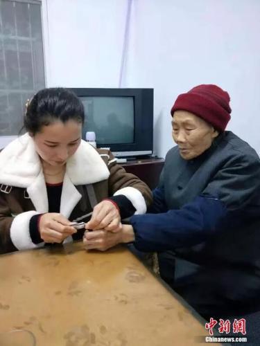 Một nàng dâu cắt móng chân cho mẹ. Ảnh: Chinanews.