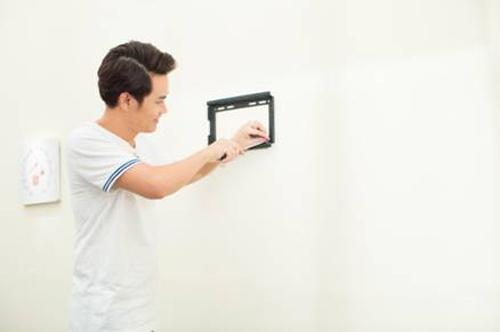 MC Hồng Phúc tự tay lắp đặt giá treo tivi mà không cần máy khoan hay tắc kê chuyên dụng như trước.