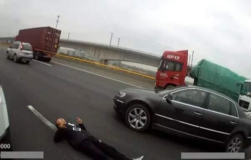 Chàng trai trẻ nằm ăn vạ trên đường cao tốc, mong cảnh sát sẽ chụp hình mình, gửi cho bạn gái để cô đến chăm sóc anh. Ảnh:Qianjiang Evening News.