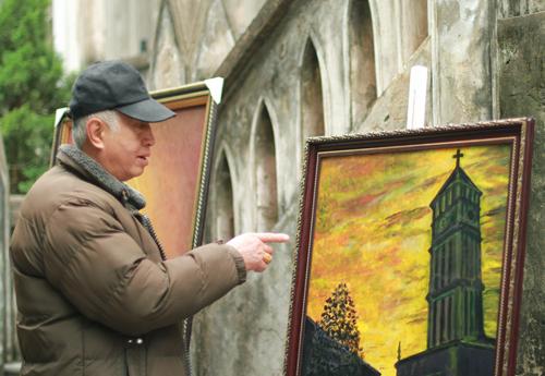 Ông Tiến trầm ngâm rất lâu trước bức tranh Nhà thờ Lớn, một trong số hơn chục tranh đang được trưng bày tại đây. Ảnh: Phan Dương.