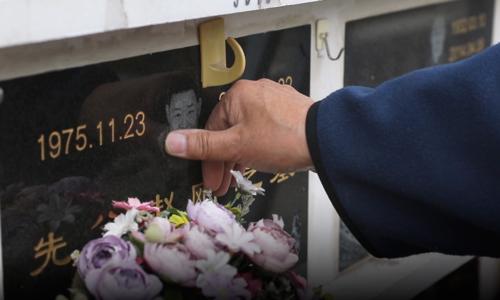 Ông Zhao chạm vào hình con trai quá cố trên tấm bia mộ anh tại Bắc Kinh. Ảnh:Sixth Tone.