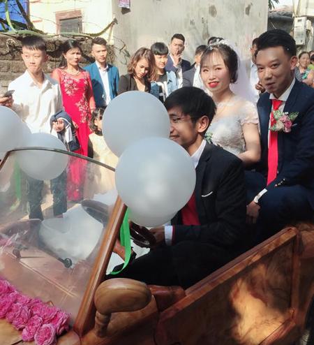 Cô dâu chú rể tươi cười trên chiếc xe gỗ tự chế.