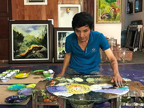 Họa sĩ Đoàn Việt Tiến tại xưởng vẽ ở nhà. Ảnh: Kim Anh