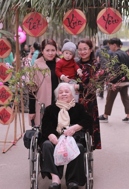 Cụ Đính đi hội chợ Tết ở viện dưỡng lão ngày 18/12 âm lịch. Con dâu, cháu và chắt của cụ đến chơi. Ảnh: Diên Hồng.