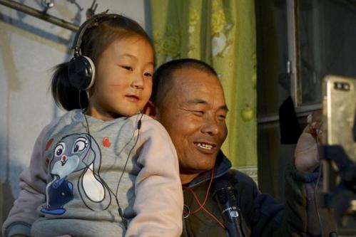 Tian và con gái ngồi trước màn hình điện thoại giao lưu với người hâm mộ mỗi đêm. Ảnh: Todayonline.