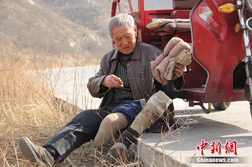Từ chân núi, ông Sanxiao phải tháo chân giả để bò lên chỗ trồng cây. Ảnh: China News.