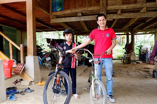 Anh Tuyến (áo đỏ) tặng cho Chiến chiếc xe đạp thương hiệu Canada, chuyên địa hình núi dốc. Ảnh: Nguyễn Công Tuyến.