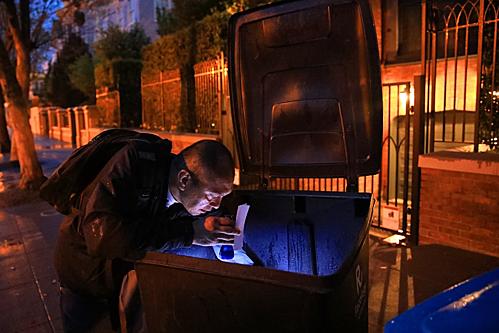 Với một chiếc đèn pin, người đàn ông săm soi các thùng rác. Ảnh: New York Times.