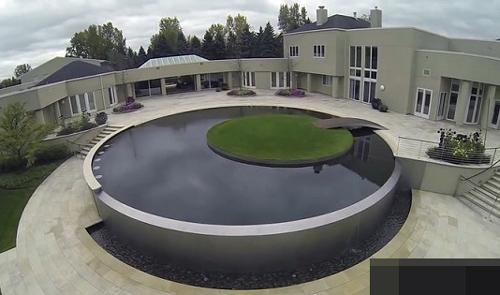 Không gian ngoài trời rộng rãi, thoáng mát với sân tennis, một hồ bơi vô cực với hòn đảo ở giữa, thảm cỏ xanh.
