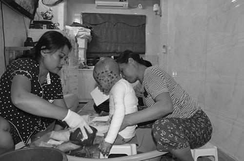 Mỗi lần tắm cho con, chị Lan (áo đen) phải mất ít nhất 3 tiếng đồng hồ dù có người giúp đỡ. Ảnh: T.Lan.