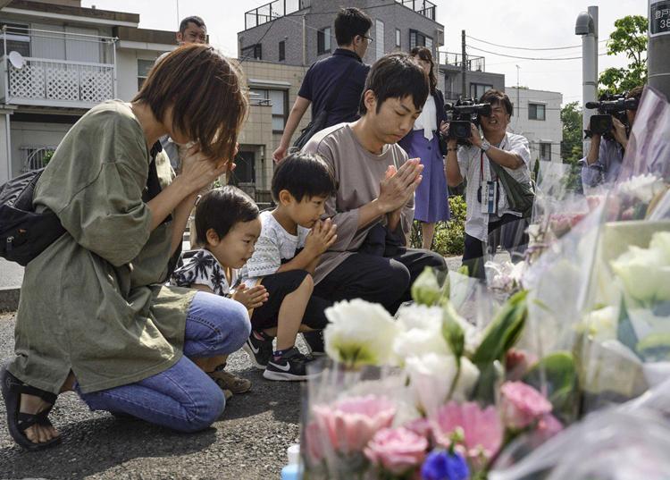 Mọi người cầu nguyện tại khu vực nơi xảy ra vụ tấn công giết người ởKawasaki, nơi một người đàn ông dùng dao đâm chết cha con một cô bé và làm bị thương hơn 15 người gần một trạm xe bus. Photo: Kyodo.