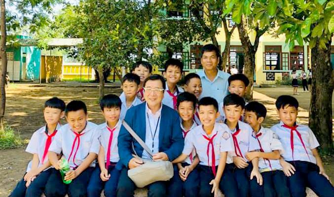 Ông Takahashi cùng thầy hiệu trưởng và học sinh trường tiểu học Junko ngày 14/5, nhân chuyến về thăm của ông. Ảnh: Trần Văn Nam.