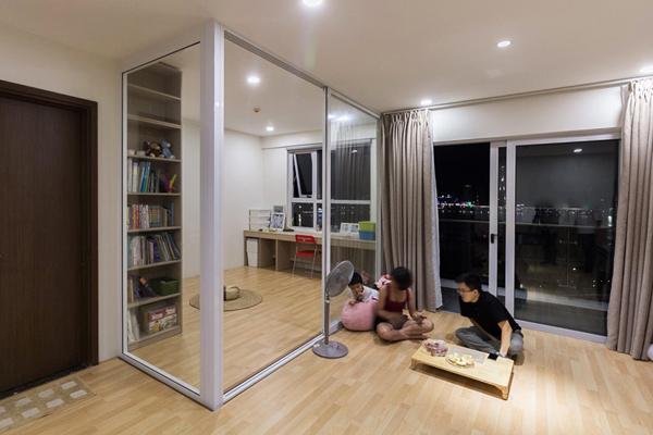 Tường phòng ngủ chính đập bỏ thay bằng cửa kính lùa để không gian thoáng, còn phòng khách hiện đang dùng một chiếc bàn nhỏ ăn uống, tiếp khách. Ảnh: Hồng Mỹ.