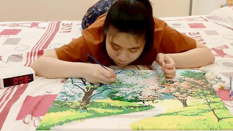 Vân Anh làm tốt các công việc thiên về tỉ mẩn. Cô thiếu nữmất vài tháng tô bức tranh số hóa phức tạp (tranh tô màu theo số). Ảnh: Hồng Vân.
