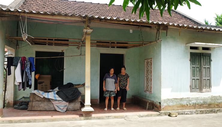 Bà Sáu đứng bên người chị gái Nguyễn Thị Ổn. Hiện tại, nỗi sợ lớn nhất của bà là nhà đổ, vì khôngcó xi măng, sắt thép. Ngôi nhà đã xuống cấpsau 11 năm.Ảnh: Hải Hiền.