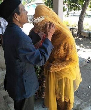 Ông Sudirgo, 83 tuổi, hôn người vợ mới cưới trong buổi lễ. Ảnh: worldofbuzz.