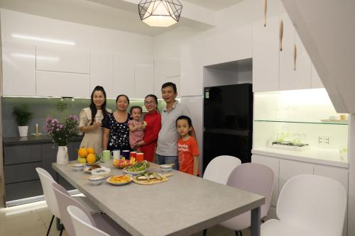 Gia đình anh Tân- chị Hồng quây quần trong gian bếp mới - nơi gắn liền sợi dây thắt chặt tình cảm với người con nuôi ở nơi xa.