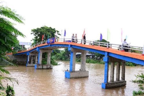 Cầu sắt mới xây chắc chắn, người dân thoải mái chạy xe máy, đi bộ trên cầu.
